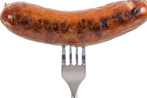 Grilled Sausage on a fork isolated on white background