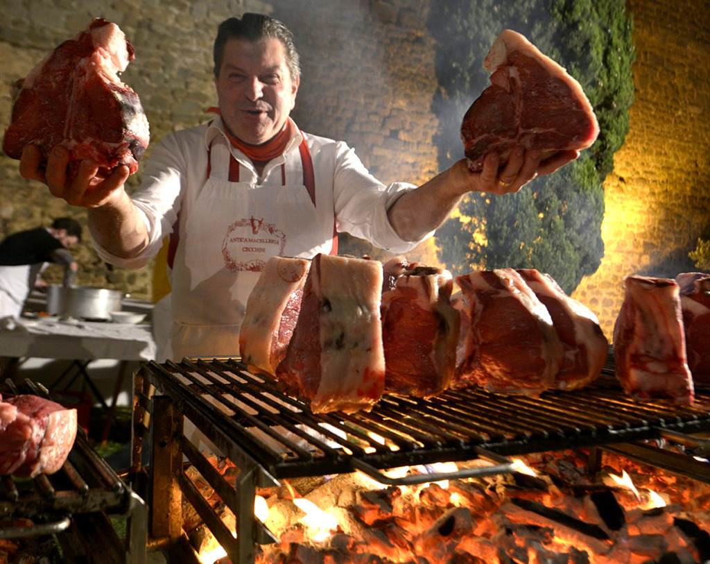 Dario Cecchini in front of charcoal grill with T-bone steaks