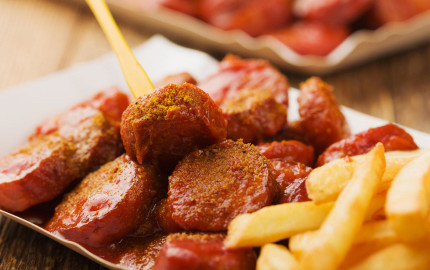 Traditional German currywurst, served with chips on disposable paper tray. Wooden table as  background.