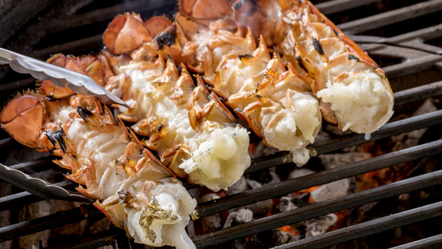 Lobster tails cooking over charcoal on barbecue grill;and; barbecue; barbecueing; celebration; charcoal; close; color; delicacy; drink; elevated; food; grate; grill; image; lobster; no; outdoor; party; people; photography; preparation; preparing; seafood; tail; texas; tongs; up; usa; view